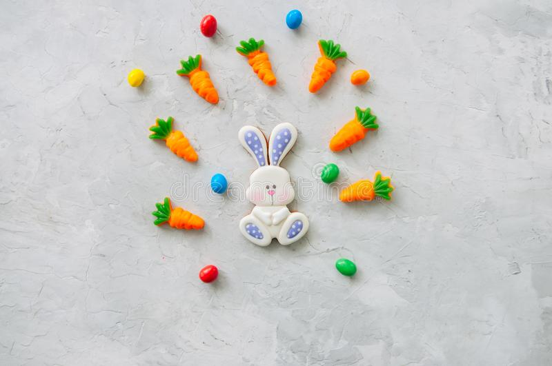 Easter bunny cookies and carrot chewing marmalade with candies o. N a white stone background. Top view and copy space stock images