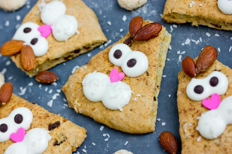 Easter bunny cookies like a funny bunnies face , Easter treats for kids. Easter bunny cookies scones decorated with cream and almonds like a funny bunnies face stock photo