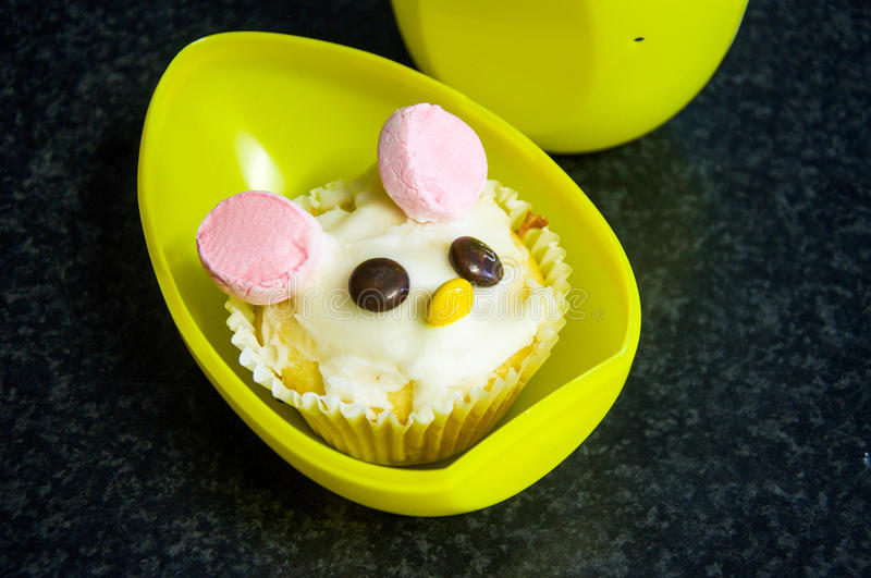 Easter Bunny Cupcake. With chocolate candy eyes and nose, and pink marshmallow ears with white frosting set in a large yellow plastic egg stock image