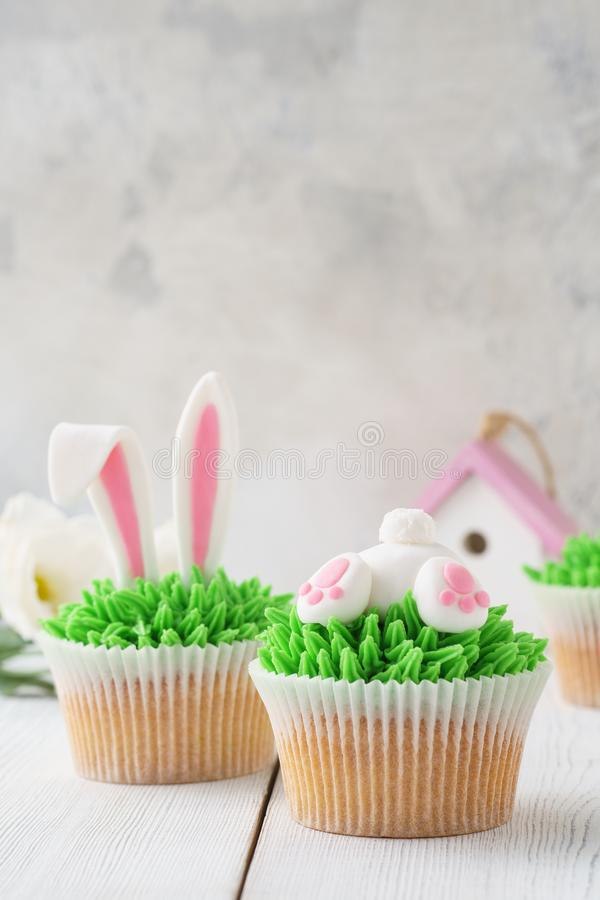 Easter bunny cupcakes, Easter food idea for kids. Easter bunny cupcakes, flowers and decoration in the background, Easter food idea for kids stock images