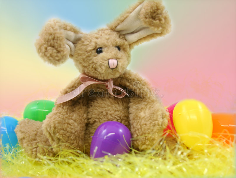 Easter bunny and eggs. A stuffed bunny with yellow Easter grass and colored eggs stock photo