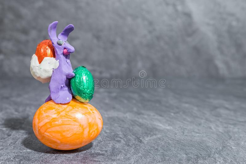 Easter bunny made of purple play dough in front of grey background.  royalty free stock photos