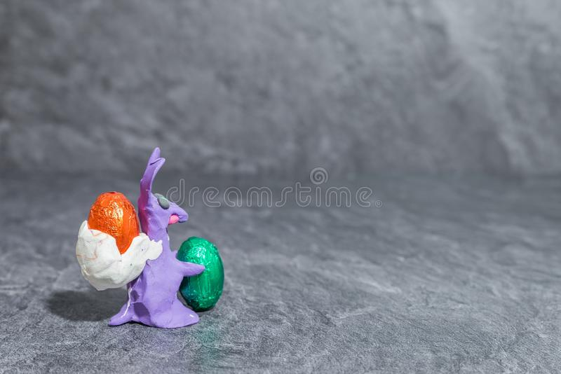 Easter bunny made of purple play dough in front of grey background.  stock images