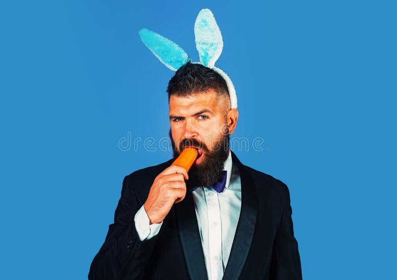 Easter bunny man nibbles a carrot like a hare. Healthy man on holiday. Easter copy space. Happy Easter. Business funny stock images