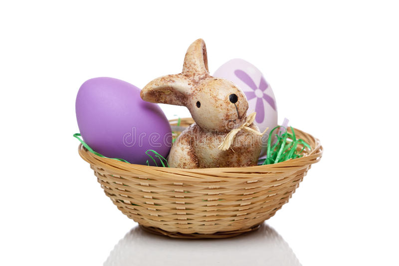 Easter bunny sitting with Easter eggs in basket royalty free stock photo