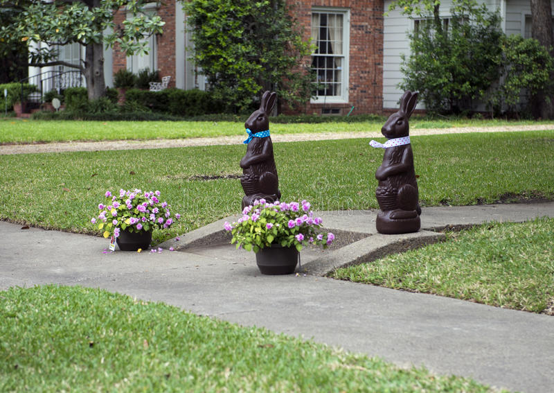 Easter Bunny statues with pots of flowers. Two brown statues of Easter bunnies welcome house visitors on the front sidewalk. Two beautiful flower baskets of pink royalty free stock images