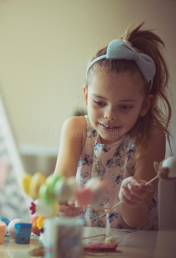 Easter bunny will be happy when he sees all these gifts for him. Little girls coloring Easter egg stock photo