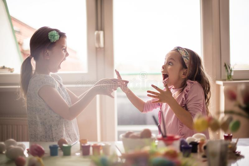 Easter bunny will get me the most gifts. Little girls coloring Easter egg stock image