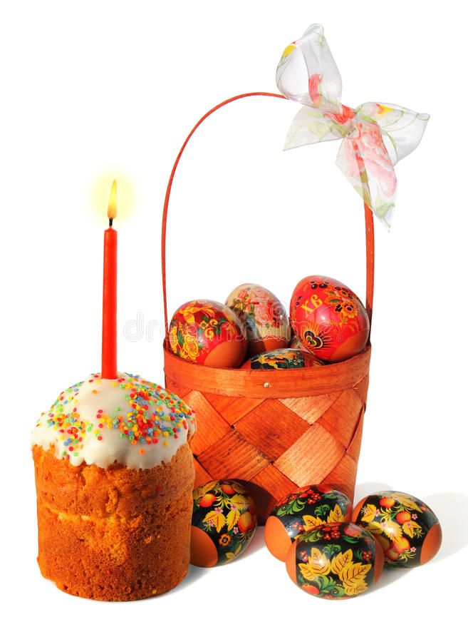 Easter cake with candle and basket with eggs royalty free stock photography