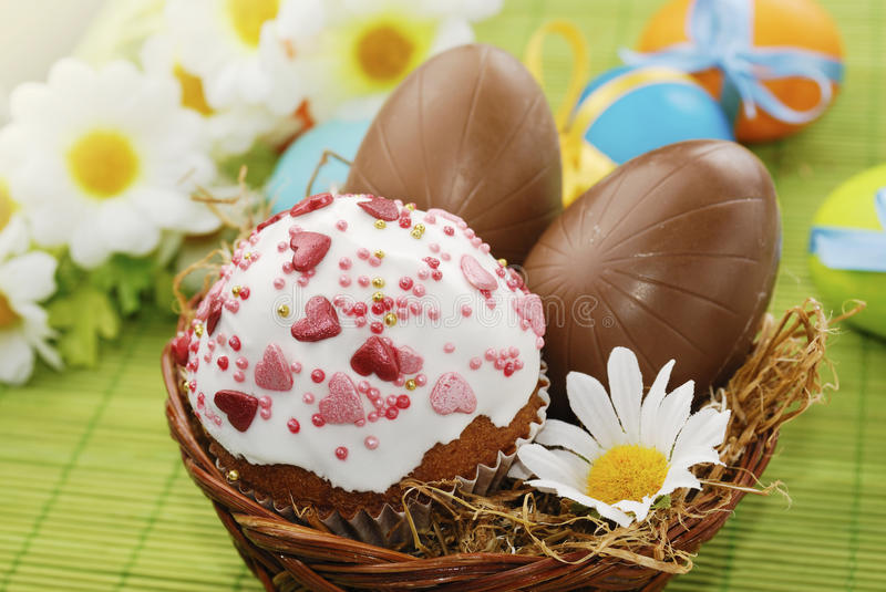 Easter cake and chocolate easter eggs. In the basket stock photography