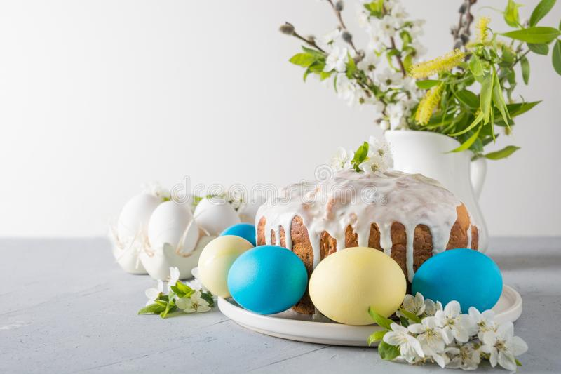 Easter cake, colored eggs on the event family table with cherry blossoms flowers. Space for text royalty free stock photo