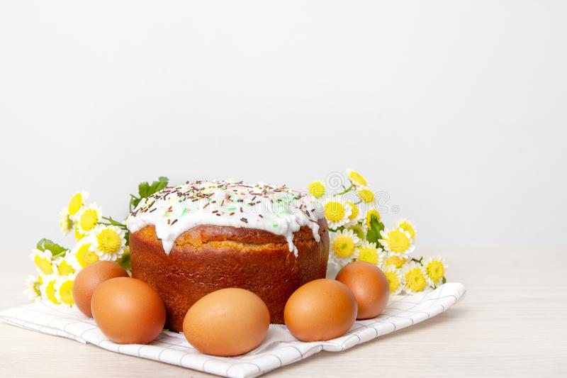 Easter cake and colored eggs  yellow flower blossoms on background. Holiday food and easter concept. Selective focus. Copyspase royalty free stock photo