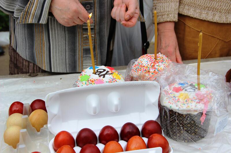 Easter cake and colorful Easter eggs on the background of a human body without a face. Orthodox Easter, preparation for stock image