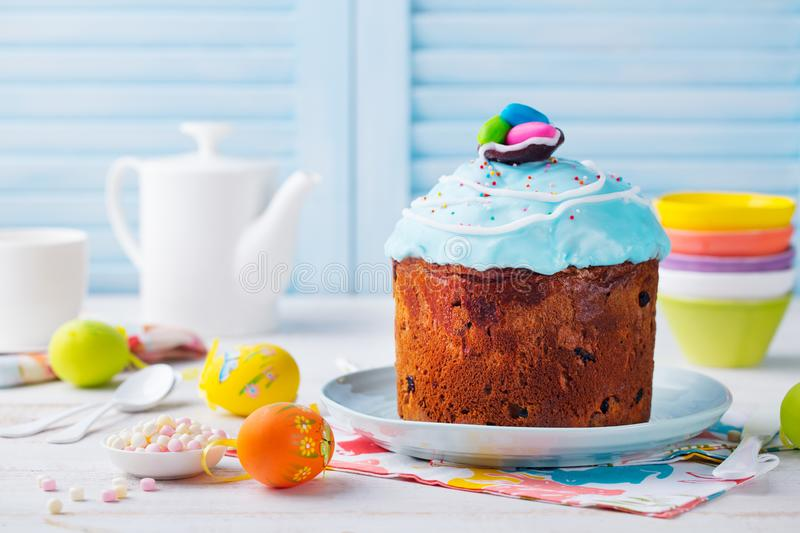 Easter cake with colorful eggs. White and blue wooden background. Copy space stock photo