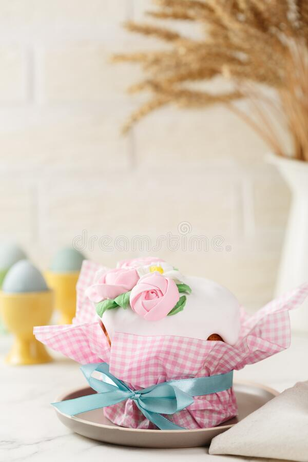 Easter cake with mastic roses. Easter cake in pink paper packaging with blue ribbon on the grey plate. Homemade festive pie with frosting and mastic floral royalty free stock photography