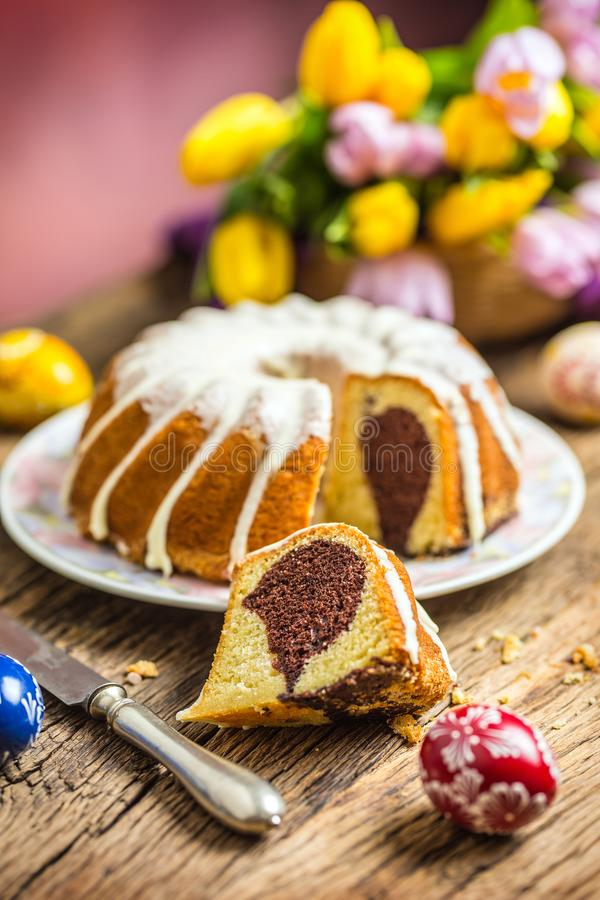 Easter Cake. Traditional ring marble cake withe easter decotation. Easter eggs and spring tulips. royalty free stock image
