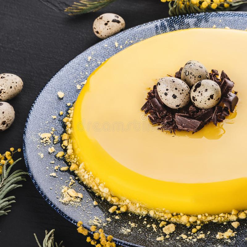Easter cake with yellow mirror glaze, chocolate, spring flowers, quail eggs on dark stone background. Happy Easter celebration royalty free stock photo