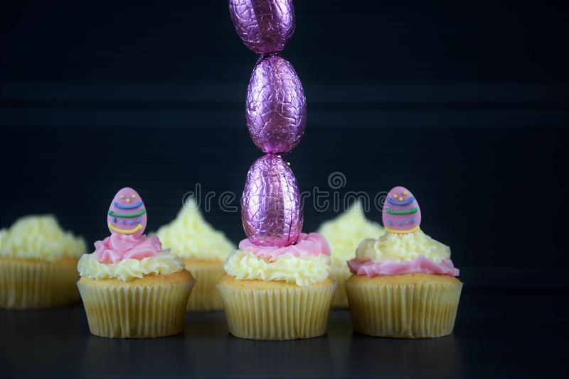 Easter cakes with chocolate eggs in a tall vertical line for creative decorations. Home made and baked vanilla sponge mini cakes or cupcakes with frosting on top stock photo