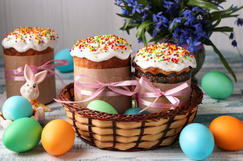 Easter cakes and colorful eggs for a bright spring holiday in a wicker basket. On a blue background stock image