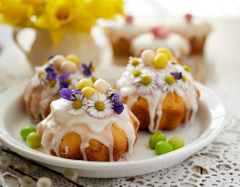 Easter cakes covered with icing decorated with spring and edible flowers and marzipan eggs on an Easter table. Easter delicious dessert royalty free stock photography