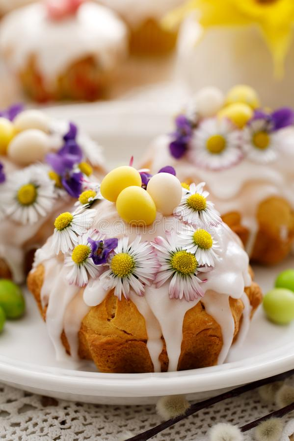 Easter cakes covered with icing decorated with spring and edible flowers and marzipan eggs on an Easter table. Easter delicious dessert stock photos