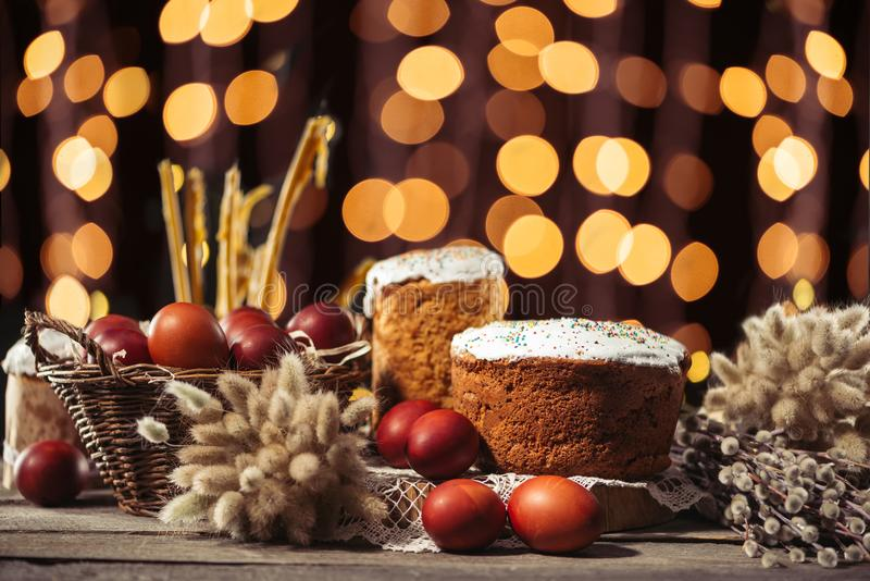 View of painted eggs in basket, willow twigs and delicious easter cakes. Easter cakes and painted chicken eggs, willow twigs and candles on wooden table with royalty free stock photo