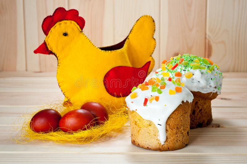 Easter cakes and painted eggs with Easter chicken on a wooden table.  stock image