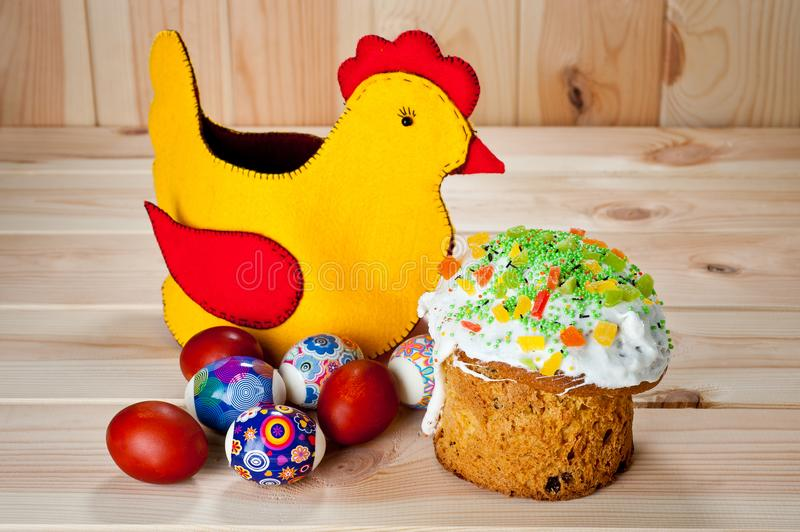 Easter cakes and painted eggs with Easter chicken on a wooden table.  stock photos