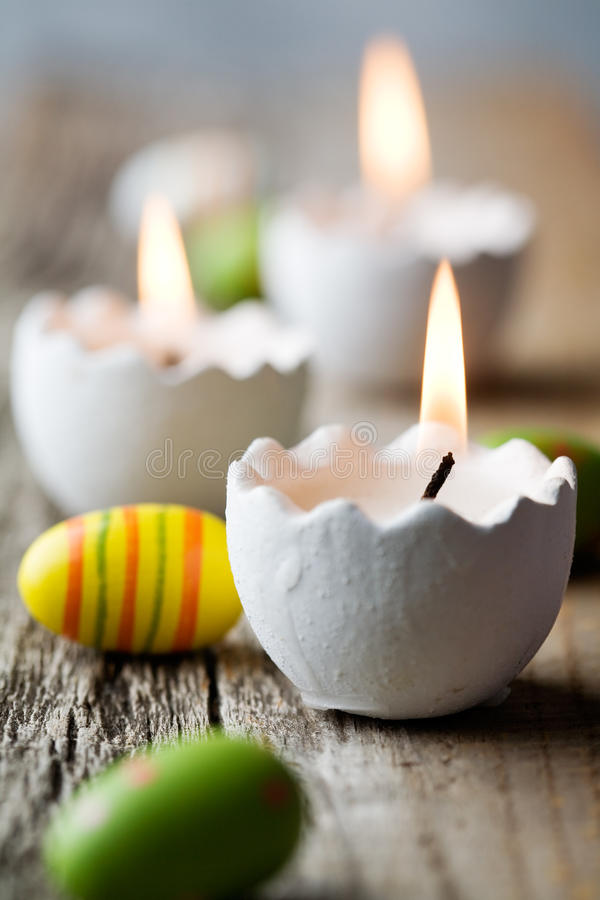 Easter candles. On wooden table with egg decorations stock photos