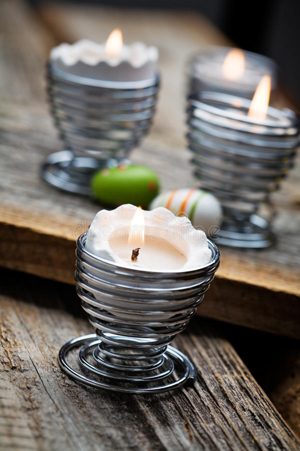 Easter candles. On wooden table with egg decorations royalty free stock image