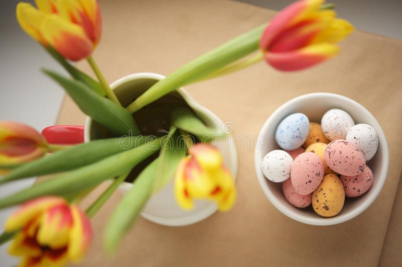 Easter candy egg and defocused tulips bouquet royalty free stock images