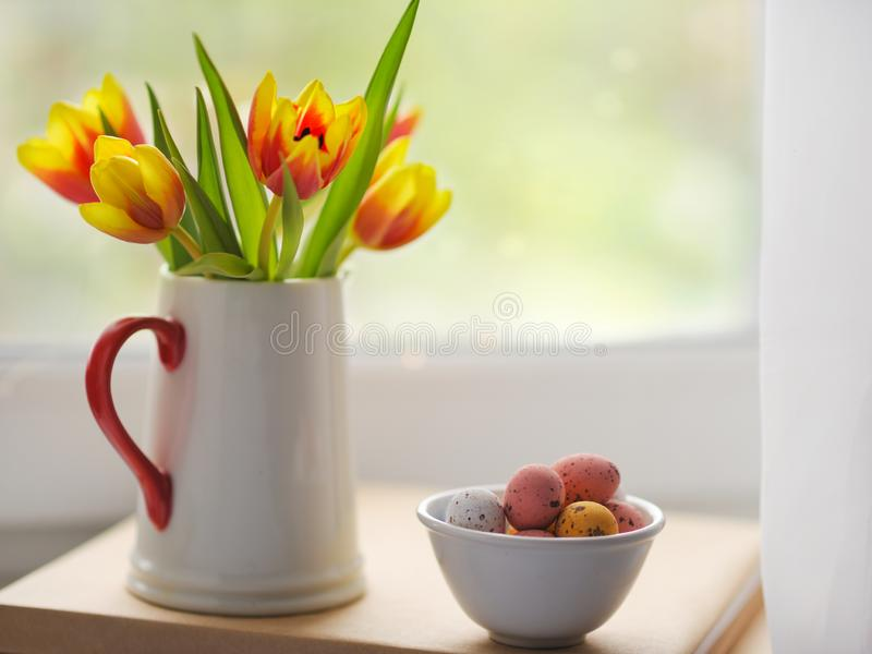 Easter candy egg and tulips bouquet stock image