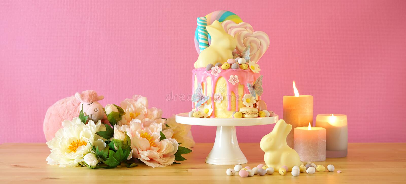 Easter candy land drip cake decorated with lollipops and white bunny. stock photography