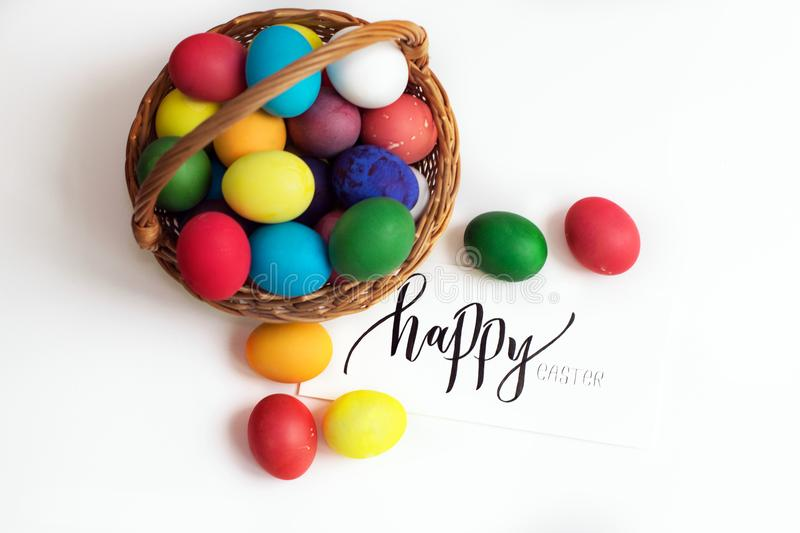 Easter card with colorful Easter eggs in a basket and calligraphic inscription `Happy Easter` royalty free stock photos