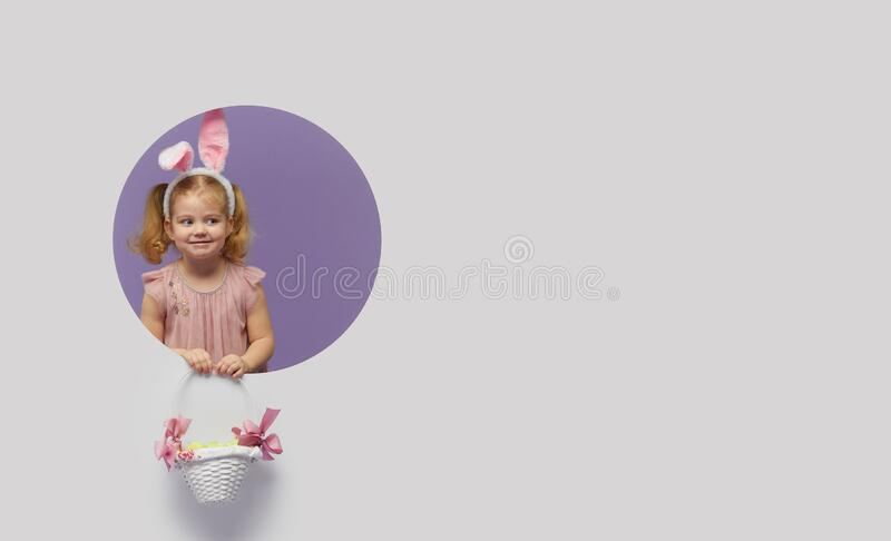 Easter card. Cute little child girl with bunny ears holding basket of Easter eggs. Child in a round hole circle in colored purple. And white background. Mockup stock photos