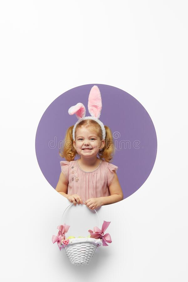Easter card. Cute little child girl with bunny ears holding basket of Easter eggs. Child in a round hole circle in colored purple stock photography