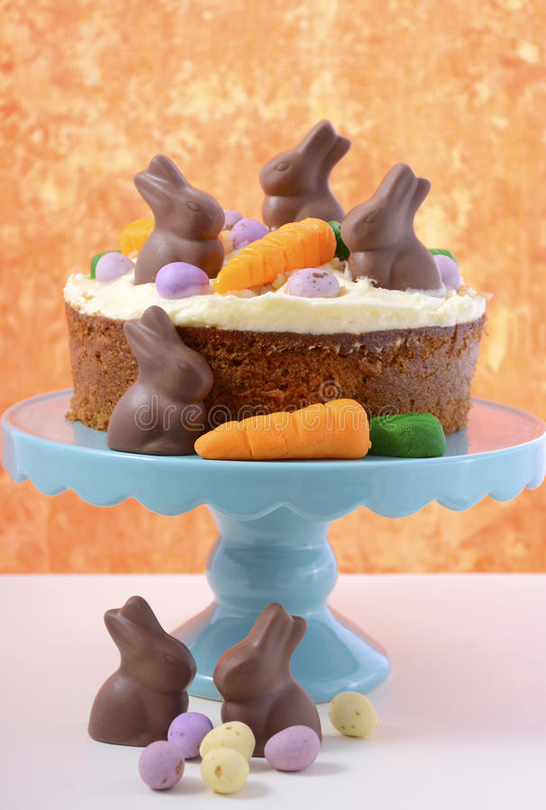 Easter Carrot Cake. Decorated with mini fondant carrots and chocolate bunnies on a white wood table with orange background royalty free stock image
