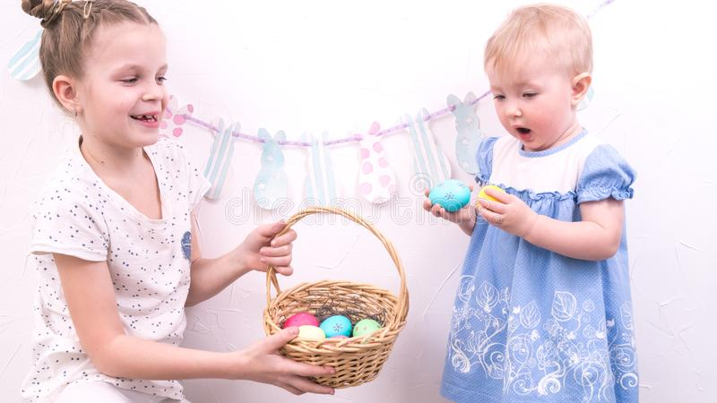 Easter celebration: The girl treats her younger sister with painted Easter eggs from a wicker basket. royalty free stock photos