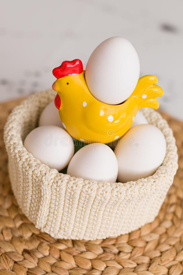 Easter celebration at home. A bright yellow hen with white organic eggs in a knitted pot. stock photography