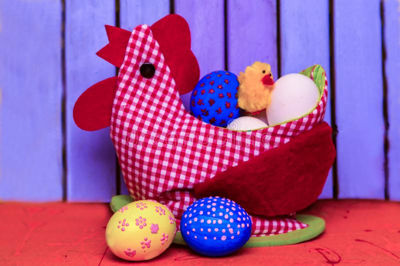 Easter chicken from red fabric and with felt inserts with a special place for storing eggs. And with a small toy chicken on his back against the background of a stock photos