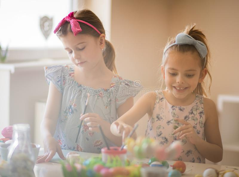 Easter is a children`s holiday. Little girls coloring Easter egg stock photo