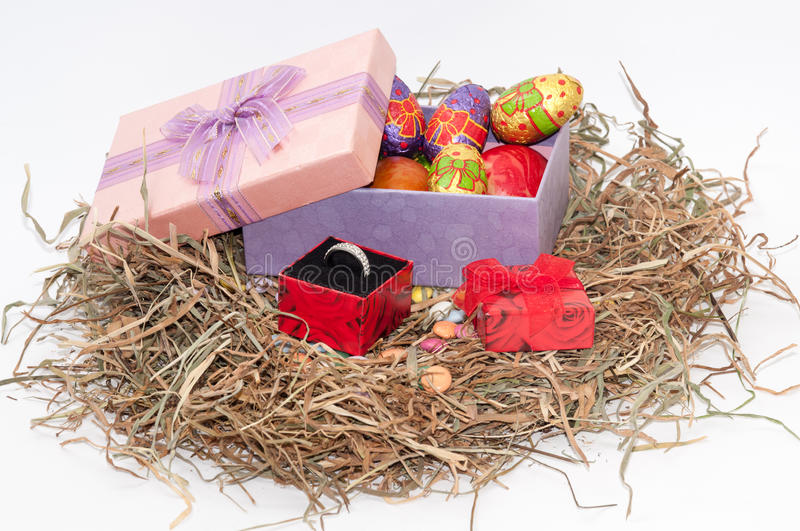 Easter chocolate and chicken eggs in pink box in the nest with g. Olden ring royalty free stock photos