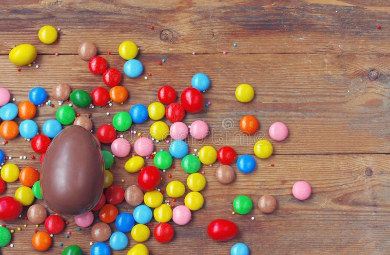Easter chocolate egg, colorful candy on wooden table top view stock photo
