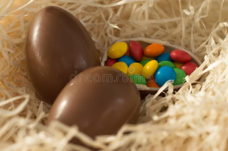 Easter. Chocolate eggs with multicolored candies lie in a nest on a wooden white table royalty free stock images