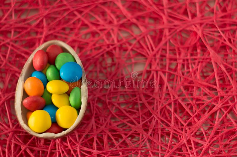 Easter. Chocolate eggs with multicolored candies lie on a pink background royalty free stock photo