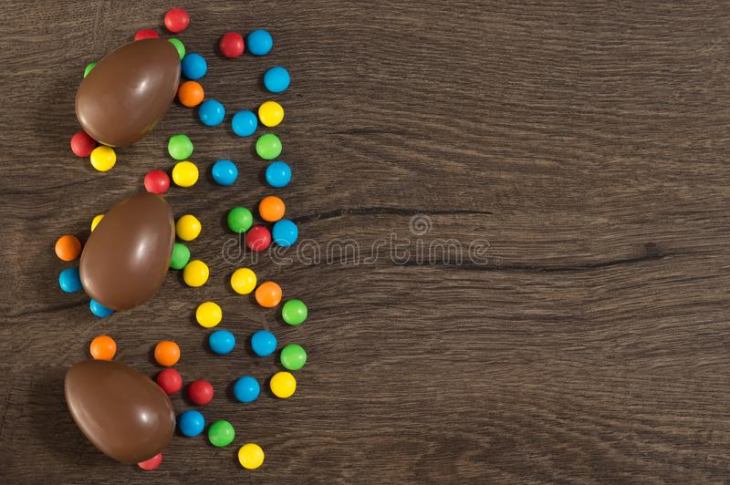 Easter. Chocolate eggs with multicolored candies lie on a wooden brown table royalty free stock image