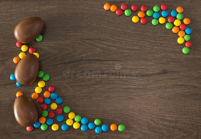 Easter. Chocolate eggs with multicolored candies lie on a wooden brown table stock photos