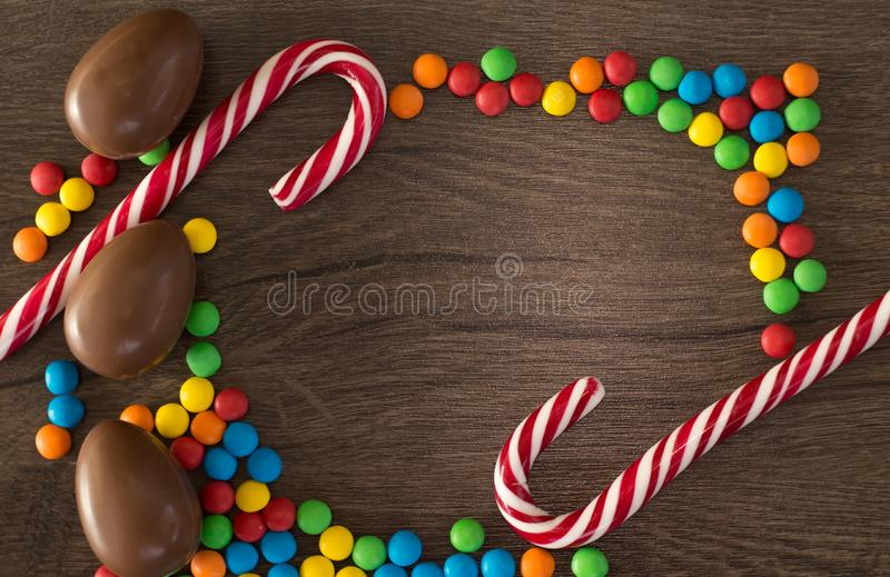 Easter. Chocolate eggs with multicolored candies lie on a wooden brown table stock image