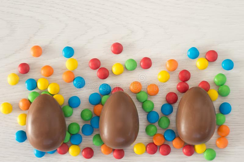 Easter. Chocolate eggs with multicolored candies lie on a wooden white table stock photography