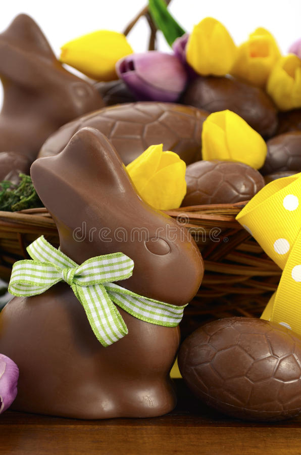 Easter chocolate hamper of eggs and bunny rabbits. Happy Easter chocolate hamper of eggs and bunny rabbits in large basket with yellow and pink purple silk tulip stock photos